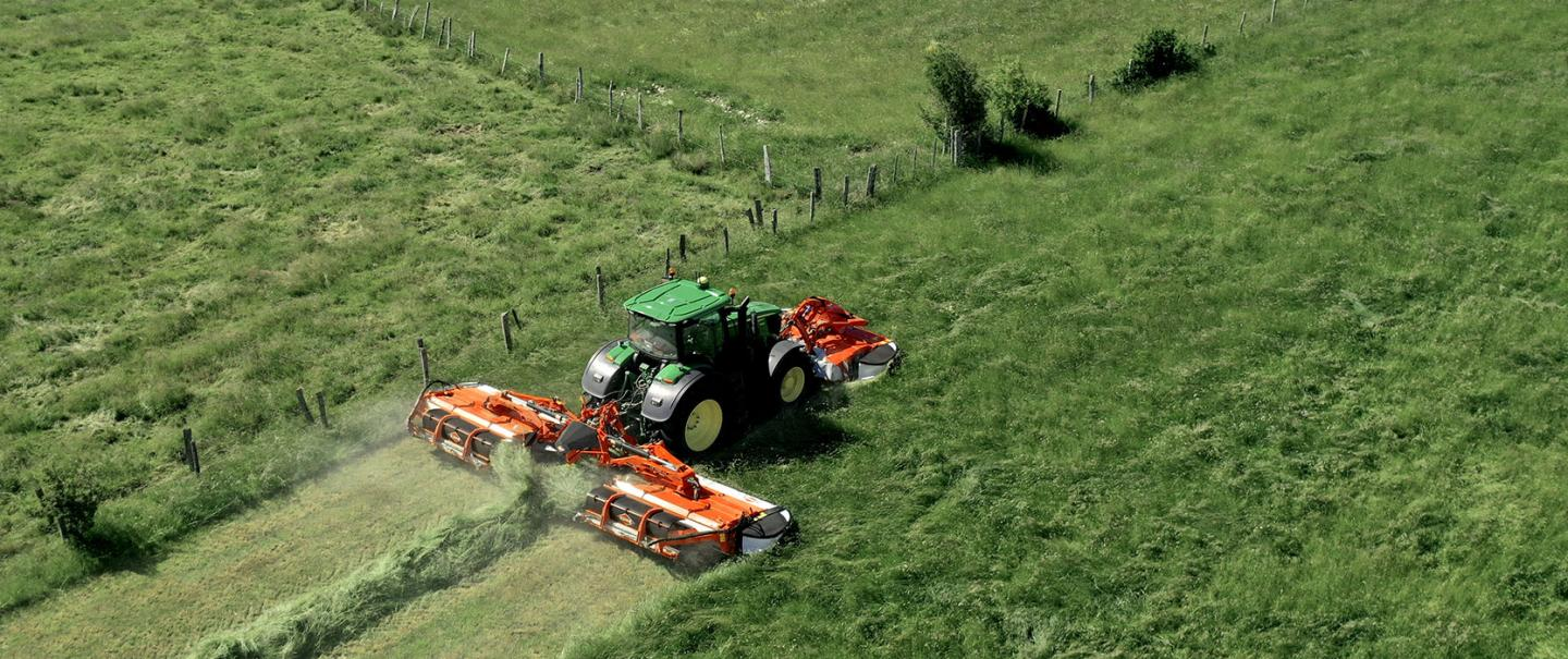 The mower conditioner with swath grouper FC 9330 RA at work in grassland, on the field boundary.