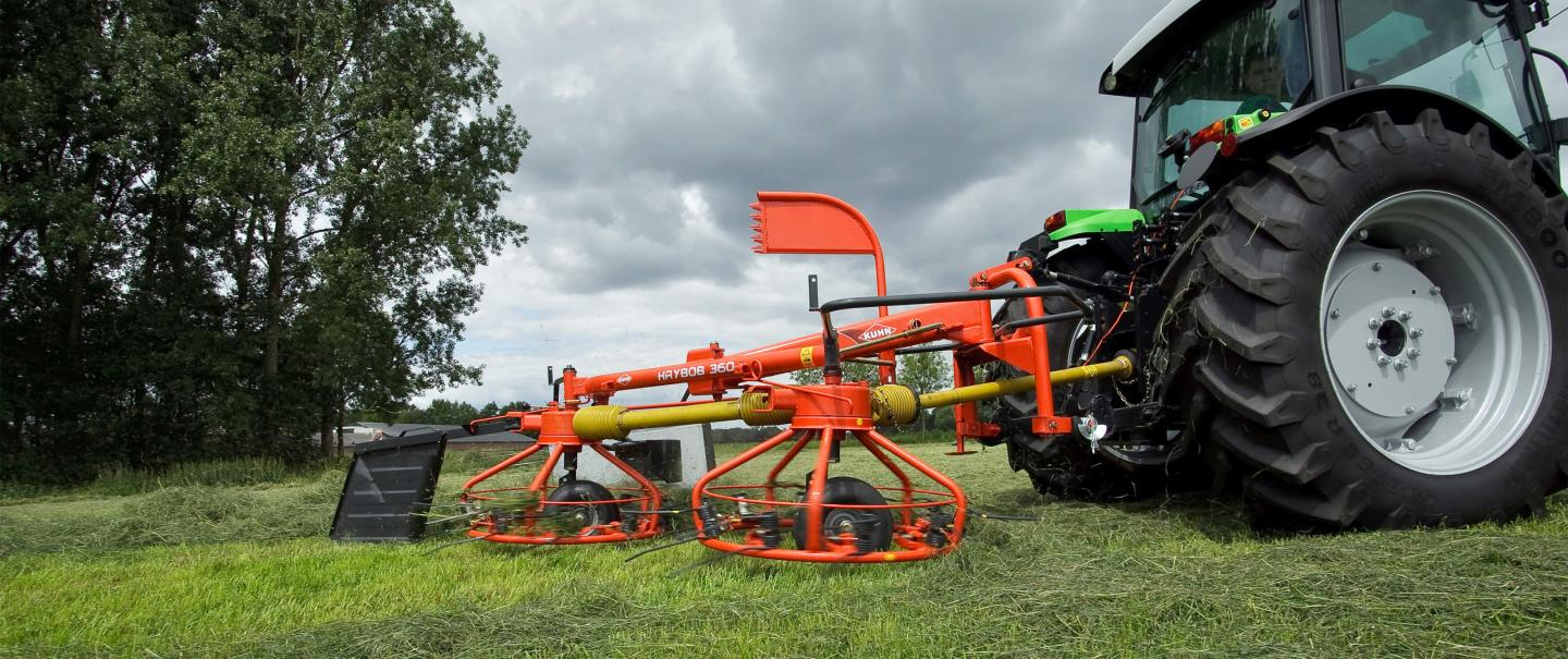 The HAYBOB 360 making a windrow under a cloudy sky.
