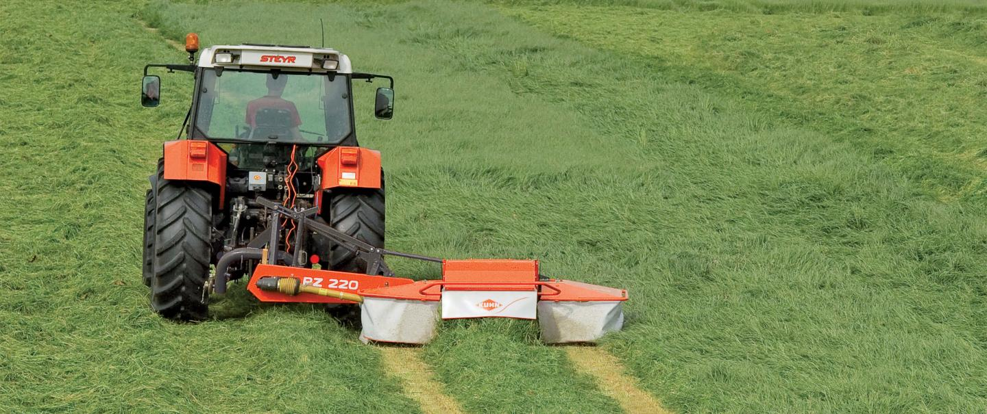 PZ 220 drum mower with conditioner is mowing gras on a flat field