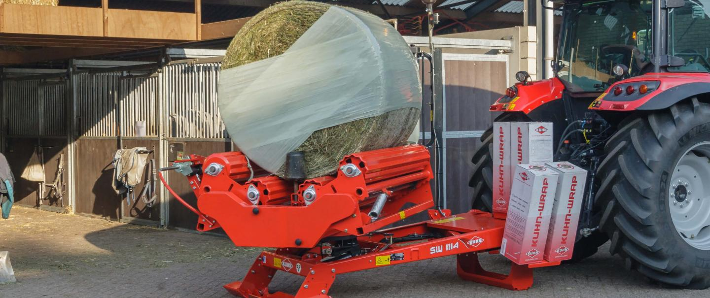 A KUHN SW1114 wrapping a round bale in front of a horse stable.